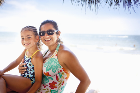 Smiling mother and daughter enjoying tropical beach