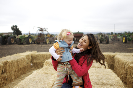 Mother and daughter enjoying playing on hay bales