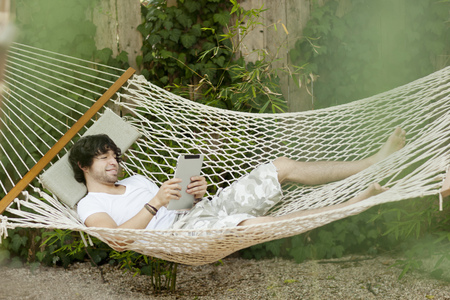 Mixed race man laying in hammock using digital tablet