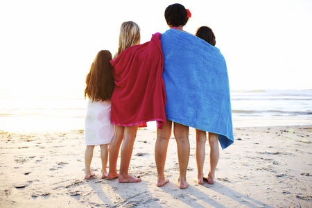 Girls wrapped in towels standing on beach LANG_EVOIMAGES