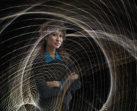 Serious mixed race businesswoman surrounded by swirling lines LANG_EVOIMAGES