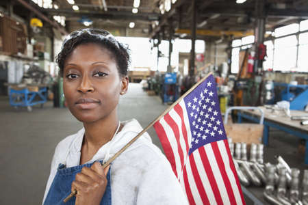 Black worker standing in factory with American flag LANG_EVOIMAGES