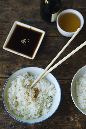 Bowl of rice and chopsticks with sauces