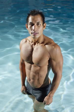 Pacific Islander man standing in swimming pool