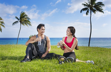Couple drinking water after exercise at waterfront LANG_EVOIMAGES