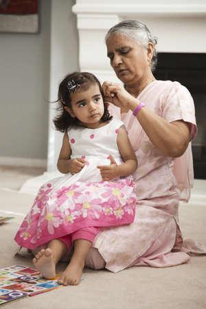 Asian grandmother fixing granddaughters hair