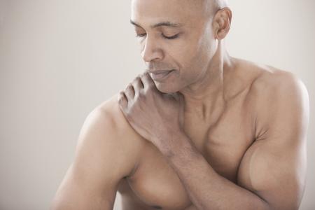 Black man rubbing his shoulders