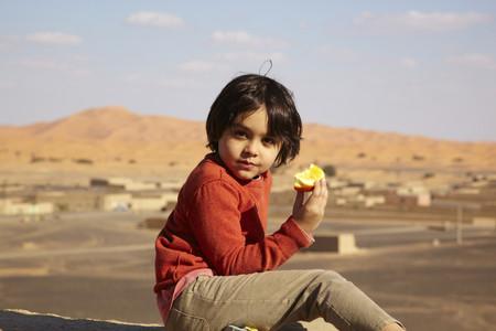 Mixed race boy eating fruit