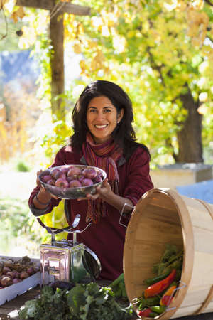 Ecuadorian woman weighing garden vegetables