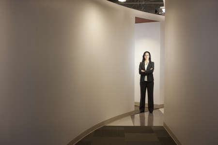 Mixed race businesswoman standing in office hallway LANG_EVOIMAGES