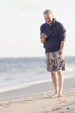 Man using cell phone on beach