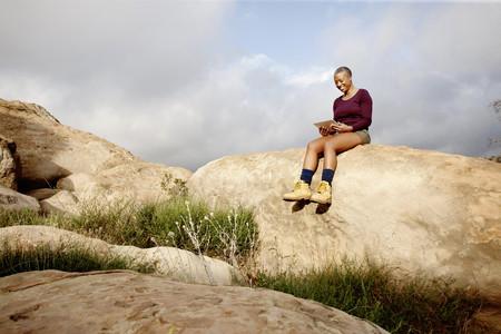 Black woman using digital tablet on rock LANG_EVOIMAGES