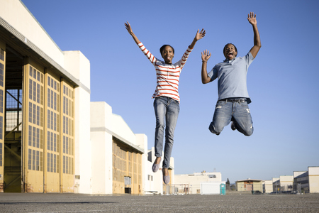 Black couple cheering and jumping LANG_EVOIMAGES