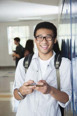 Mixed race high school student text messaging on cell phone LANG_EVOIMAGES