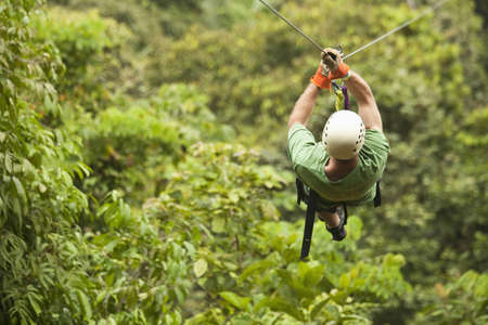 Caucasian man on zip line in forest LANG_EVOIMAGES