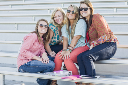 Friends sitting on bleachers LANG_EVOIMAGES