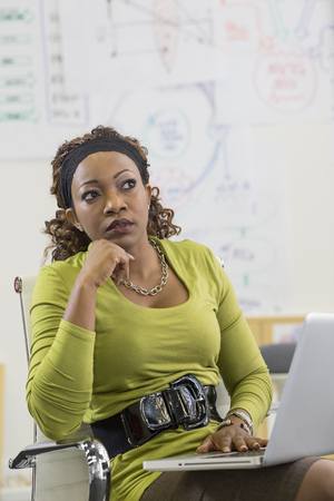 Mixed race businesswoman thinking in office LANG_EVOIMAGES