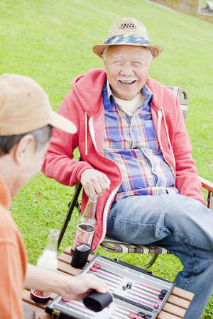 Older men playing backgammon outdoors