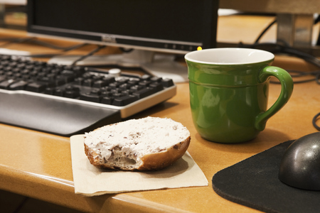 Coffee Cup and Bagel on a Desk LANG_EVOIMAGES