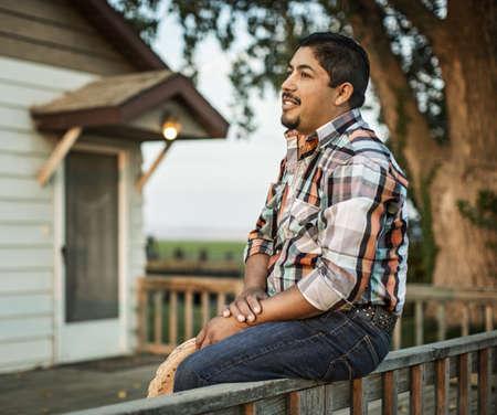 Hispanic man sitting on porch railing