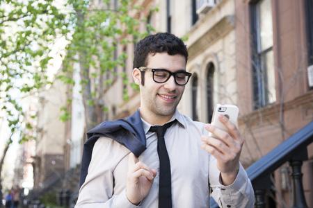 Hispanic businessman using cell phone outside LANG_EVOIMAGES