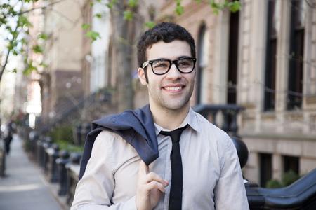 Hispanic businessman walking on city sidewalk