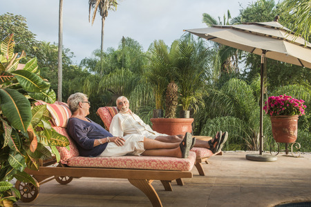 Older Caucasian couple relaxing by pool LANG_EVOIMAGES