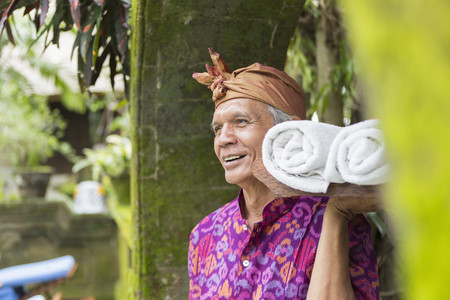 Balinese worker carrying rolled towels