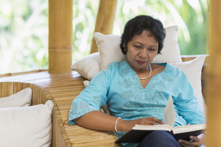 Balinese woman reading in armchair