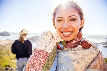 Woman wrapped in blanket on rural hillside LANG_EVOIMAGES