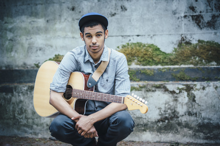 Mixed race boy with guitar crouching on urban sidewalk LANG_EVOIMAGES