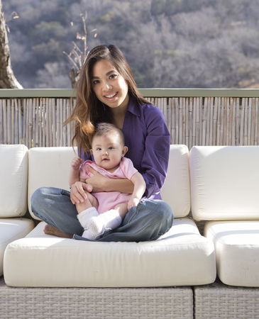 Mother holding baby girl on patio sofa