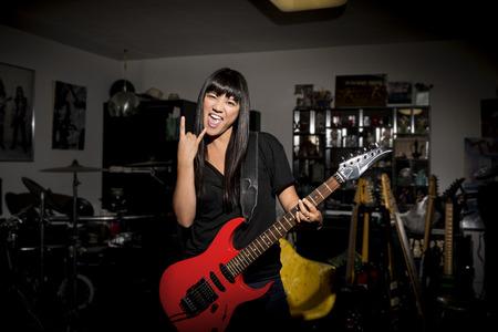 Woman playing electric guitar in basement