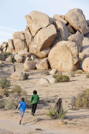Caucasian boys running in desert