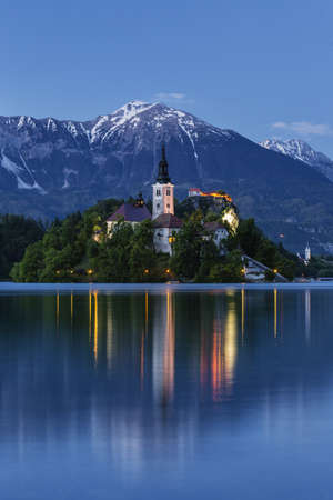 Church tower and mountains reflecting in still lake LANG_EVOIMAGES