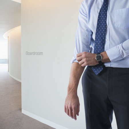 Caucasian businessman rolling up sleeve