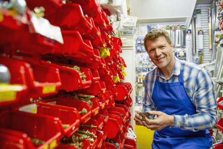 Caucasian worker holding part in hardware store