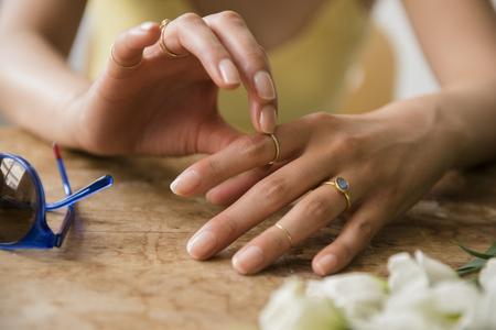 Hands of Hispanic woman wearing rings near flowers and sunglasses