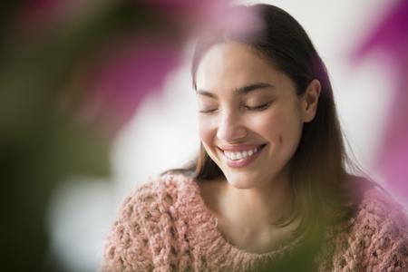 Hispanic woman smiling behind pink flowers