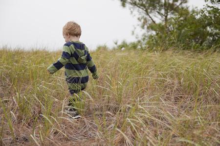 Caucasian boy walking in field of tall grass