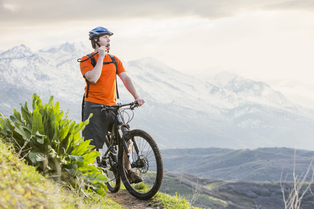 Caucasian man riding mountain bike resting and drinking water