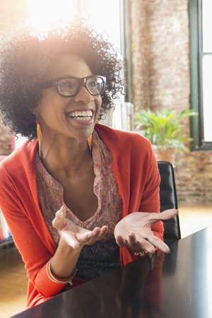 Black businesswoman gesturing at desk