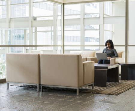 Black businesswoman using laptop in lobby armchair