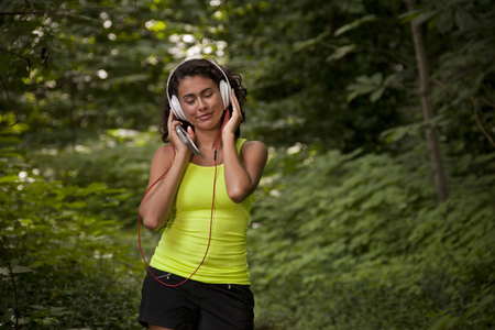 Hispanic woman listening to headphone and cell phone in forest