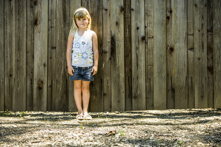 Caucasian girl standing at wooden fence