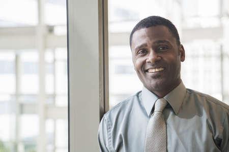 Smiling Black businessman near window