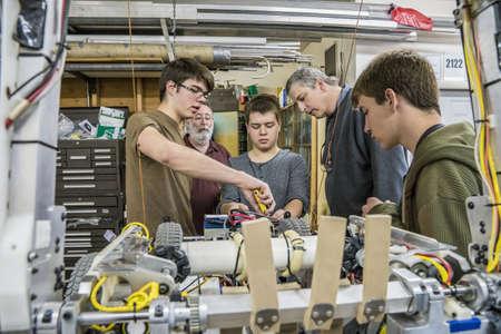 Robotics students and teacher adjusting machinery LANG_EVOIMAGES
