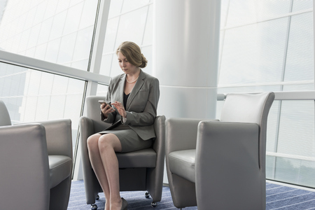 Caucasian businesswoman sitting in armchair using cell phone
