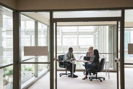 Business people using laptops in meeting beyond doorway