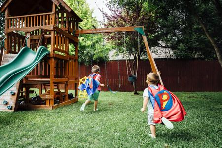 Caucasian brothers wearing superhero costumes in backyard
